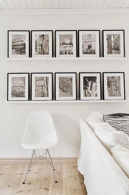 Classic black and white gallery wall with a casual leaning twist on floating shelves thin black frames and white mats keep the display clean and cohesive