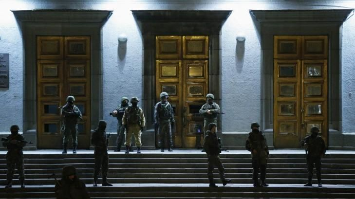 Armed men stand guard at the local government headquarters