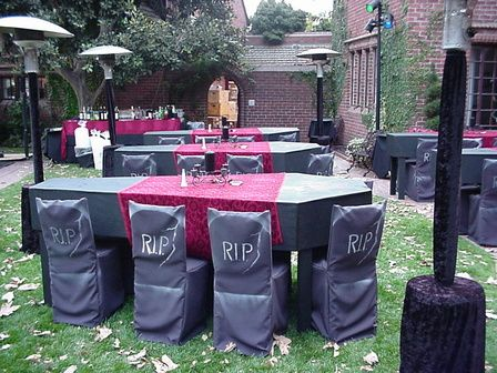Coffin table and tombstone chair slip covers.... Nice idea to have several outdoor heaters covered in black crushed velvet and it looks like there's mood lighting also..... great party idea!!!