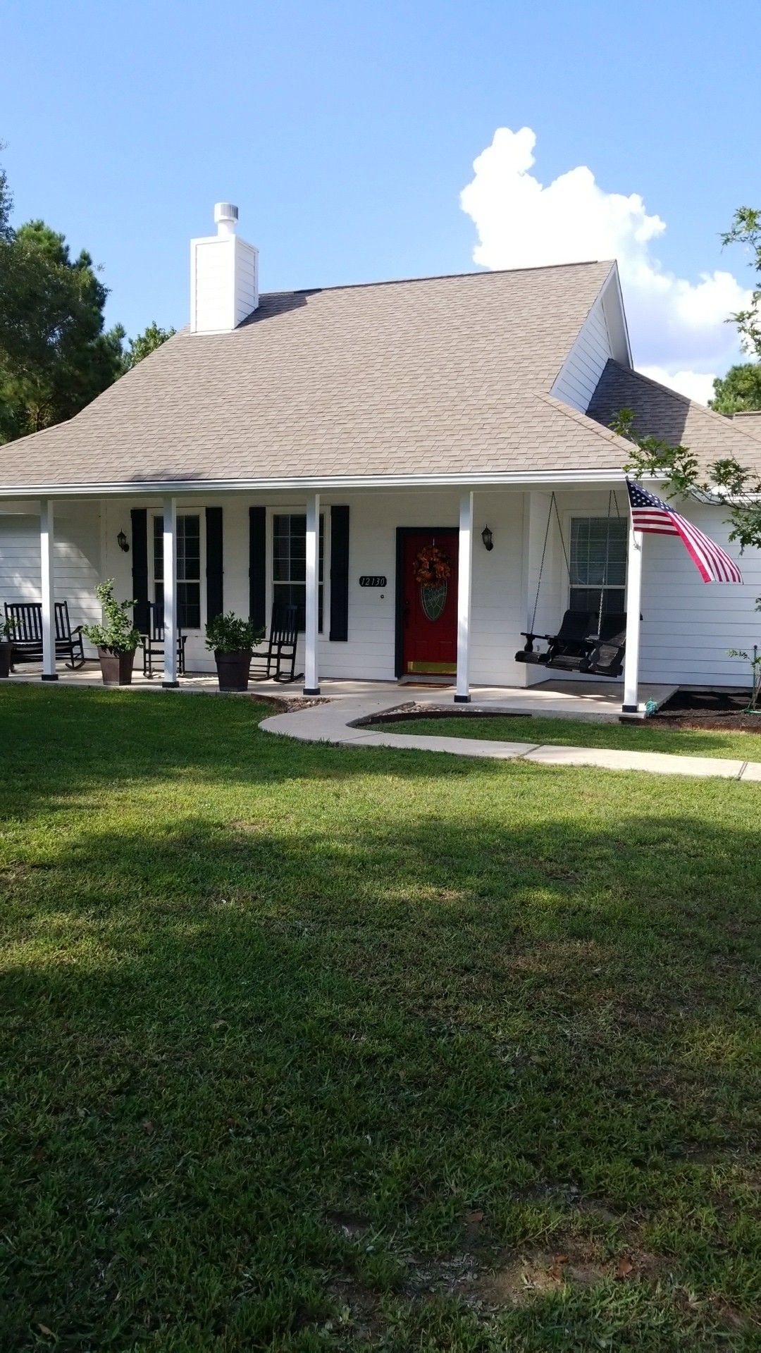 Farm House white with black shutters and red door Conroe