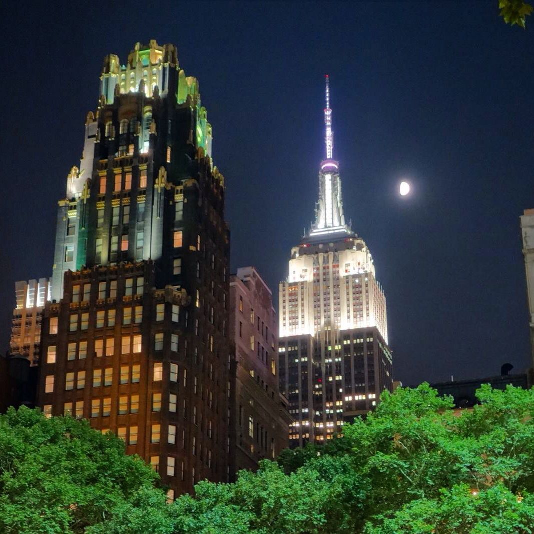 The Empire State Building Shines Above Buildings Near Bryant Belvedere Hotel