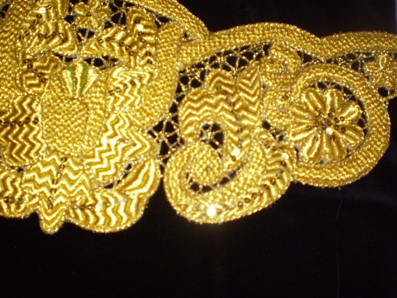 Detalle de cinturilla bordada sobre red con hilo de oro.