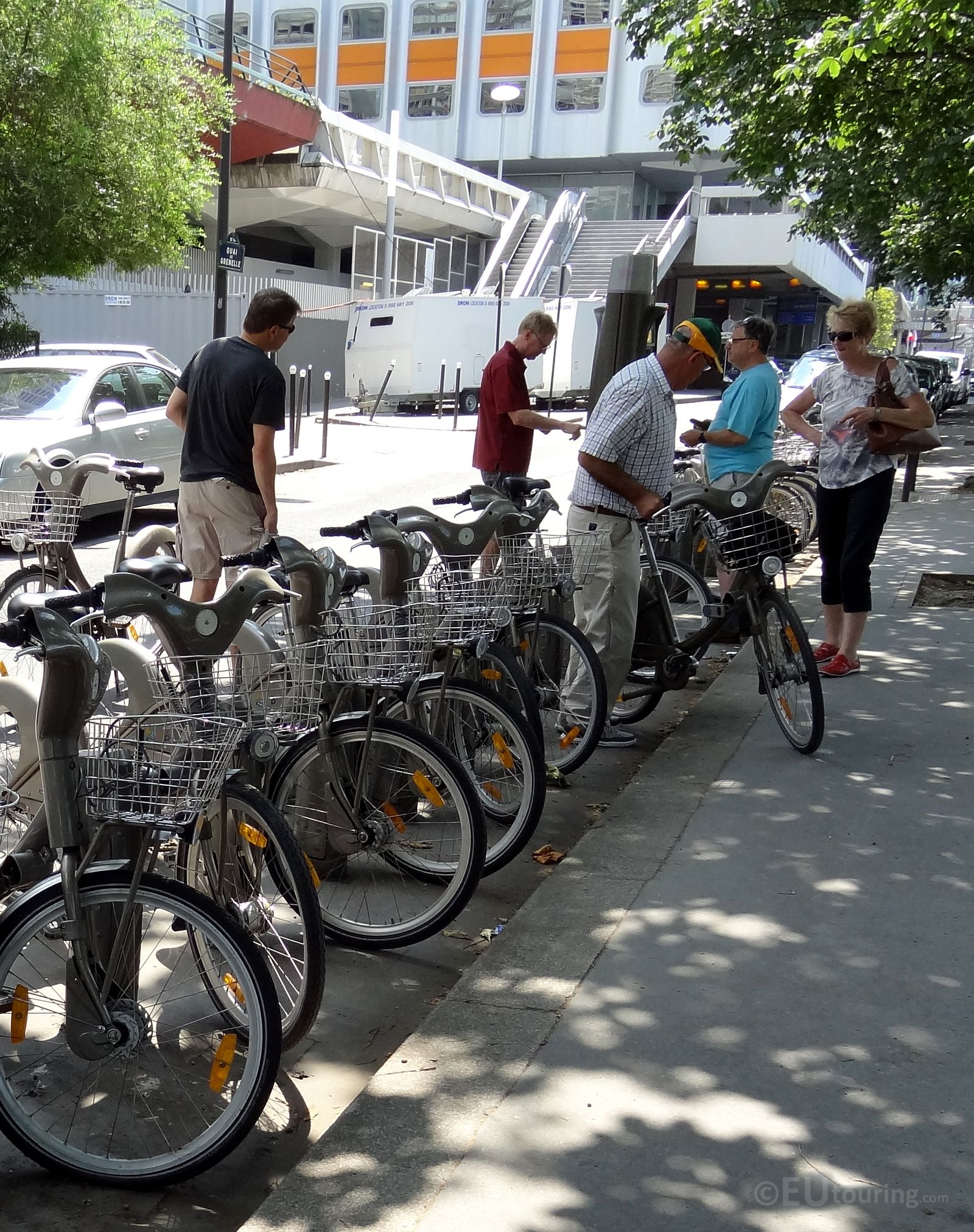 A Group Of Tourists Getting Ready To Use The Velib Bikes To Travel