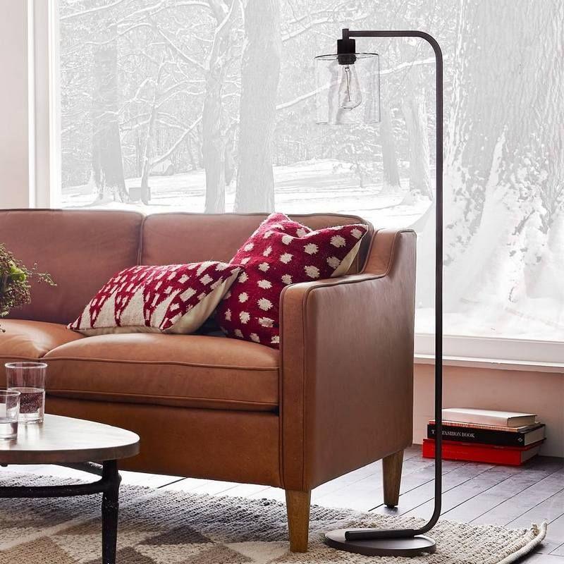 Lampadaire industriel dans le salon canapé en cuir cognac et coussins déco