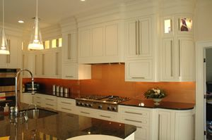 copper backsplash, white cabinets, black/dark counter, silver sink