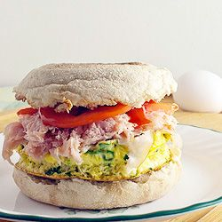 Healthy egg sandwich with spinach, ham, cheese and tomato on an english muffin.