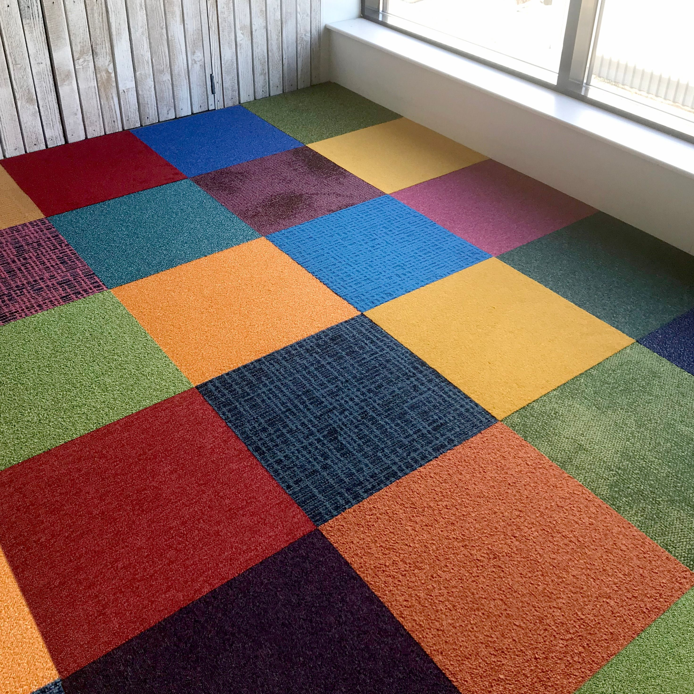 A mixture of Heuga and Interface carpet tiles in different