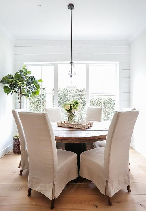 round wood dining table. Cottage Breakfast Nook Is Lined With Horizontal Shiplap Surrounding A Round Reclaimed Wood Dining Table Natural Linen Slipcovered Chairs