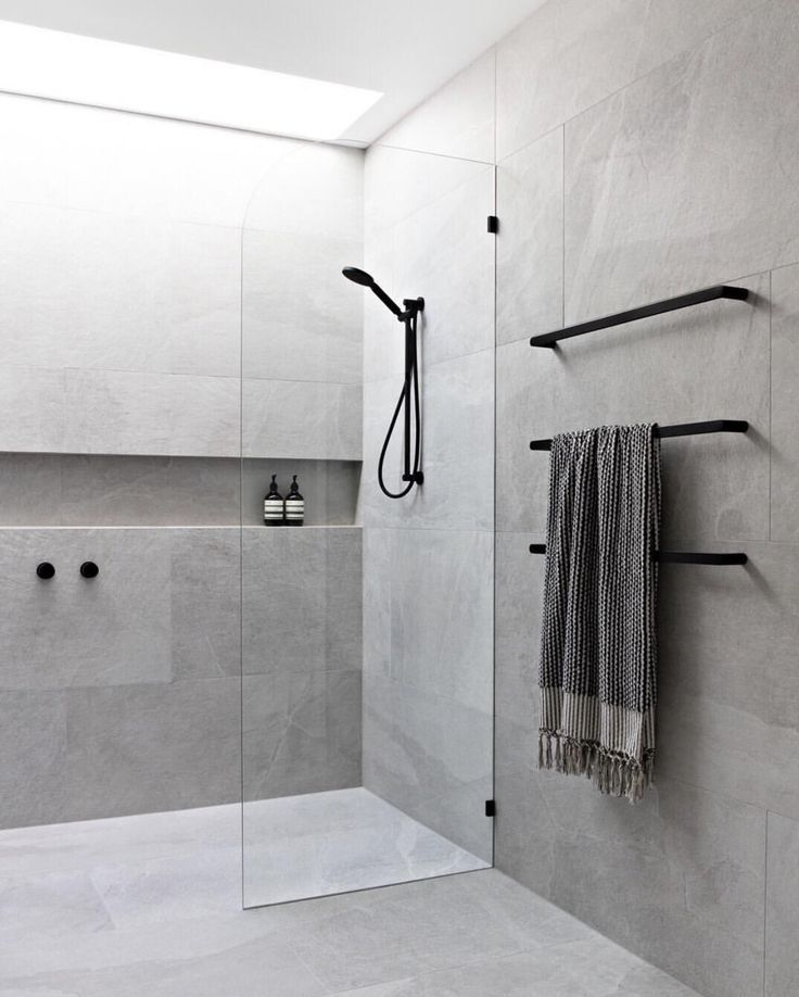 Photo of Private bathroom with skylight attaching black taps and gray tiles