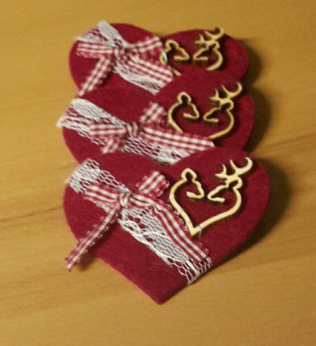 Gästeanstecker aus rotem filz mit spitze, masche und holzhirschen