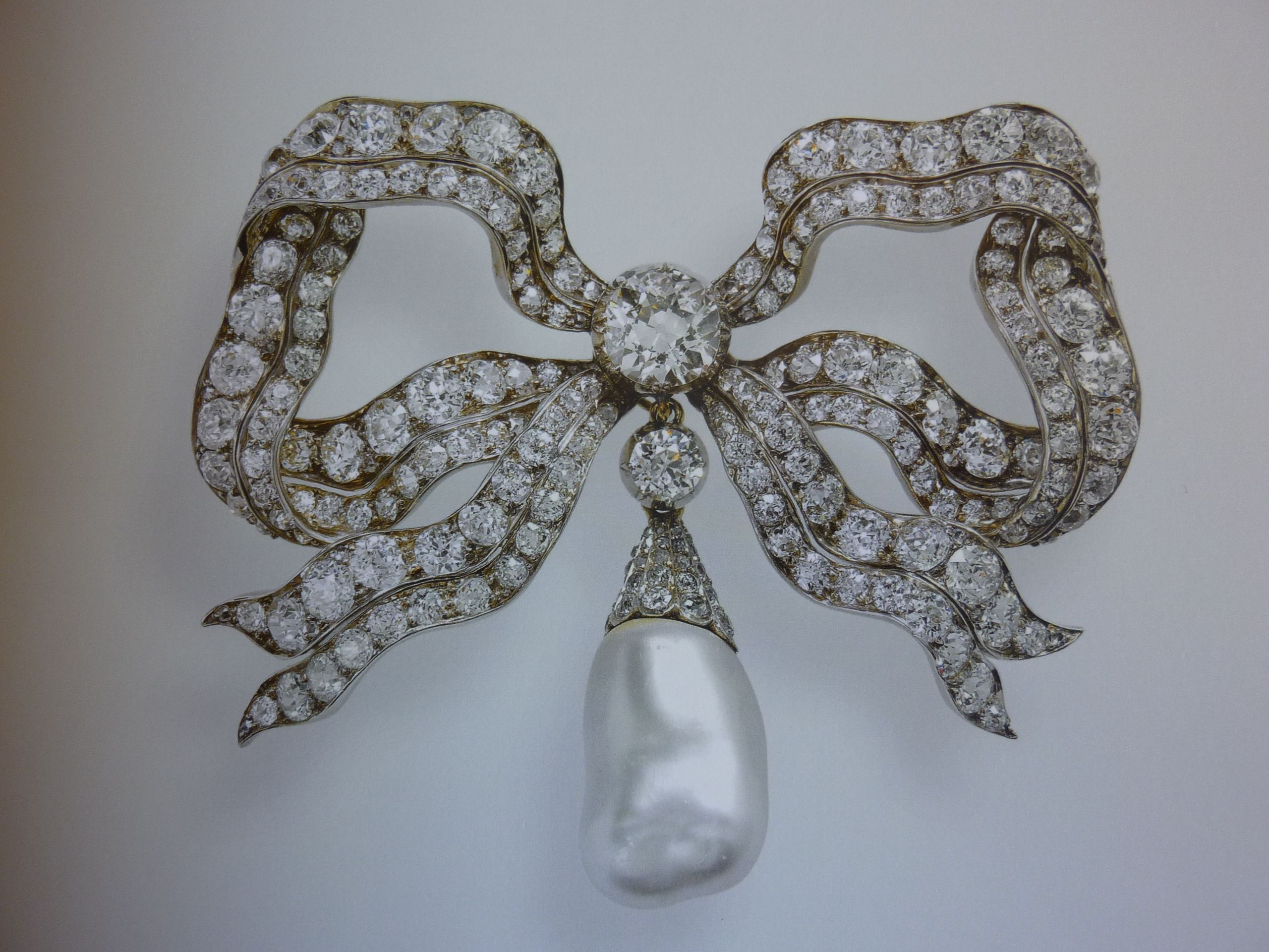 The Kensington Bow brooch: One of the Queen`s most used brooches, it is quite large so is more often used for formal events or Rememberance services. The Queen chose to wear this brooch to her mother`s funeral. It is a large diamond bow with an oriental pearl pendant. The Bow can be worn without the pendant. Queen Mary wore the brooch until she left it to the Queen in 1953.