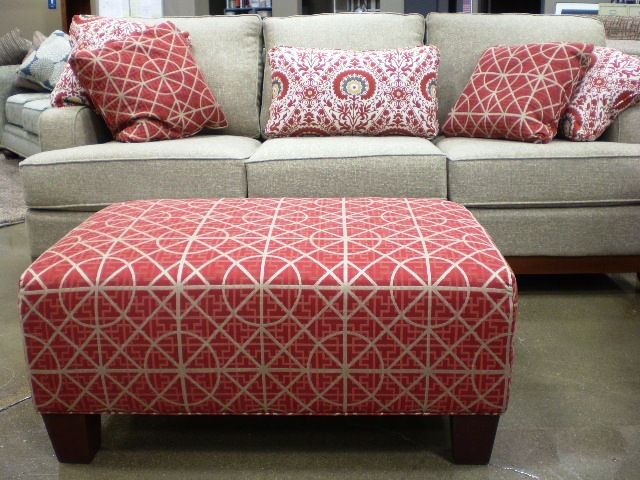 Red fabric ottoman with neutral sofa and matching accent pillows ...