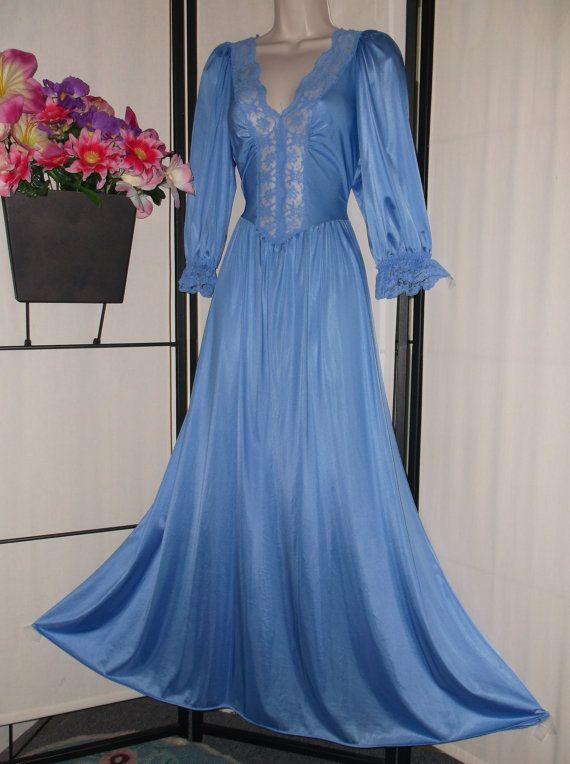 Lovely vintage Olga peignoir nightgown in a soft cornflower blue color. 1980s Style Number 92067, size Medium. 3/4 sleeves are elasticized and trimmed in lace. Stretch bodice with gorgeous lace detail in front. Modest sweep; low cut front. Very good vintage condition; light signs of wear. Beautiful! Measurements are:  Bust: 32 - 38 Waist: 25 - 35 Hips: 48 Total length: 57  Please feel free to ask me questions, and be sure to check out my other lovely vintage items for sale.  *Customers o...