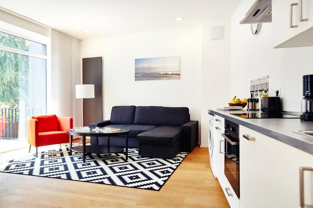 Wohnbereich mit schwarzem Ecksofa, geometrischem Teppich und - einrichtung wohnzimmer