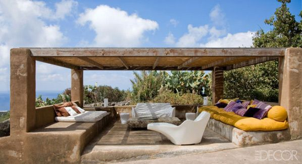 The pergola on designer Flavio Albanese's compound on the island of Pantelleria contains a Tokyo Pop lounge chair by Tokujin Yoshioka and low-slung benches covered in pillows.
