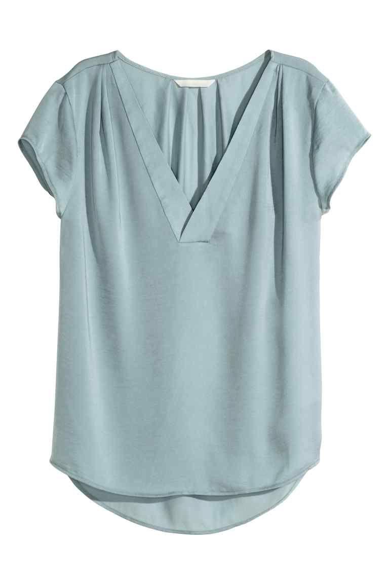 Blusa de cetim com decote em V: Blusa de cetim com mangas curtas e decote em V. Tem pregas nos ombros e na parte de trás do pescoço. Base arredondada e costas ligeiramente mais compridas.