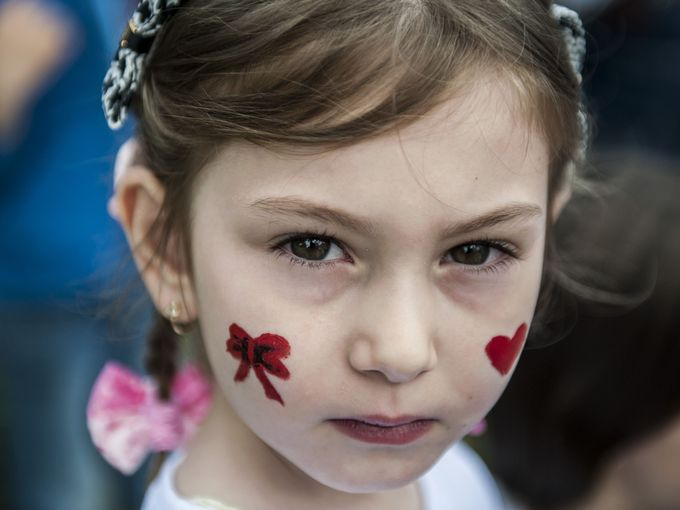 A Kosovar child with painted cheeks takes part in activities