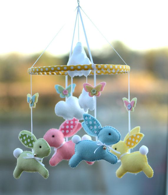 Welcome To FlossyTots  This beautiful mobile is MADE TO ORDER  This mobile consists of 4 cute bunnies handstitched using premium wool blend felt, in lemon yellow, ice blue, pink and pale mint with a dot fabric on the ears. Around each bunnys neck is a satin ribbon with a small silver bell.  These mobiles are original Flossytots designs and are carefully cut and handstitched with lots of care and attention to detail. They make a beautiful feature for a nursery or bedroom, adored by your…
