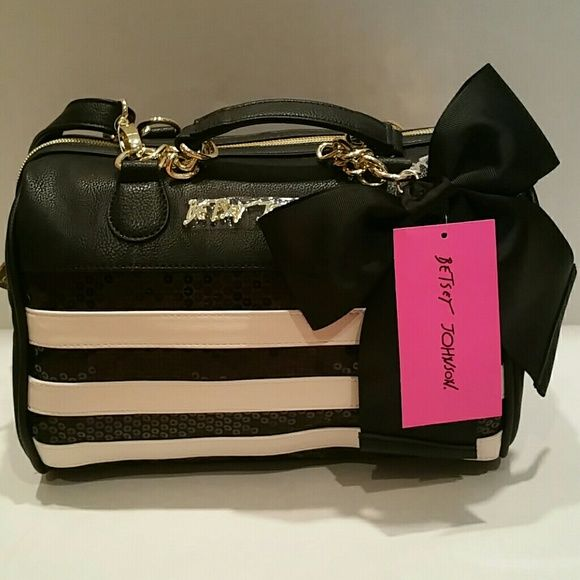 Betsey Johnson Medium Satchel Sequin stripes NWT Gorgeous bag, I want to keep it. It is a normal size bag with leather and chain handles. It also has removable cross body straps. The front is really nice with stripes of black sequins and cream faux leather stripes. It has a black ribbon bow and a gold Betsey Johnson signature on.the front. The lining is signature BJ, maroon with pink lips _ gorgeous. It is not quite as girly as some of the other bags so more adaptable for all ages. It is…