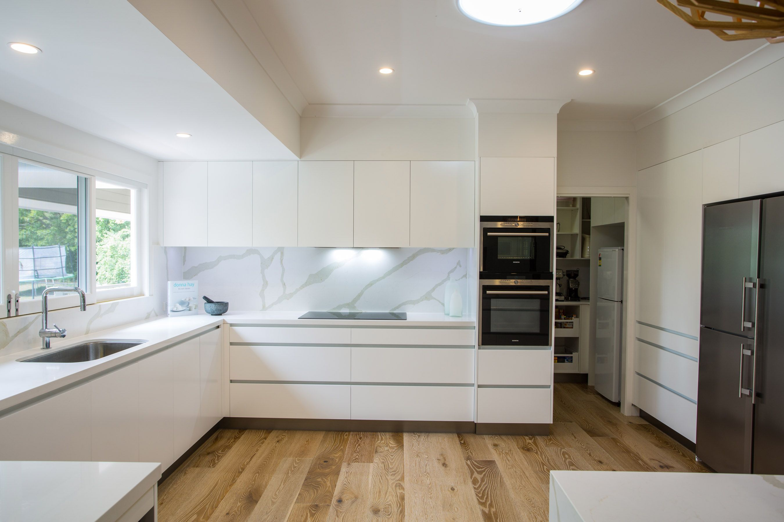 luxury contemporary kitchen with self contained butlers pantry through door way
