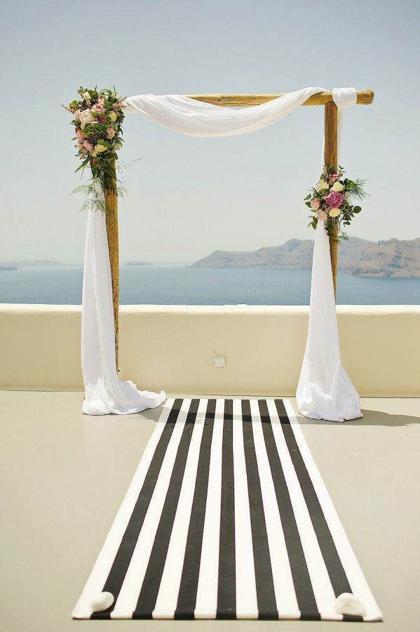 Modern al fresco wooden linen draped wedding arch: http://www.stylemepretty.com/destination-weddings/2016/10/07/this-adventure-loving-duo-tied-the-knot-in-greece-and-it-was-awesome/ Photography: Thanasis Kaiafas - http://www.thanasiskaiafas.com/