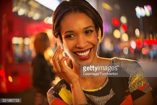 Stock Photo : Woman taking on cell phone on city street at night