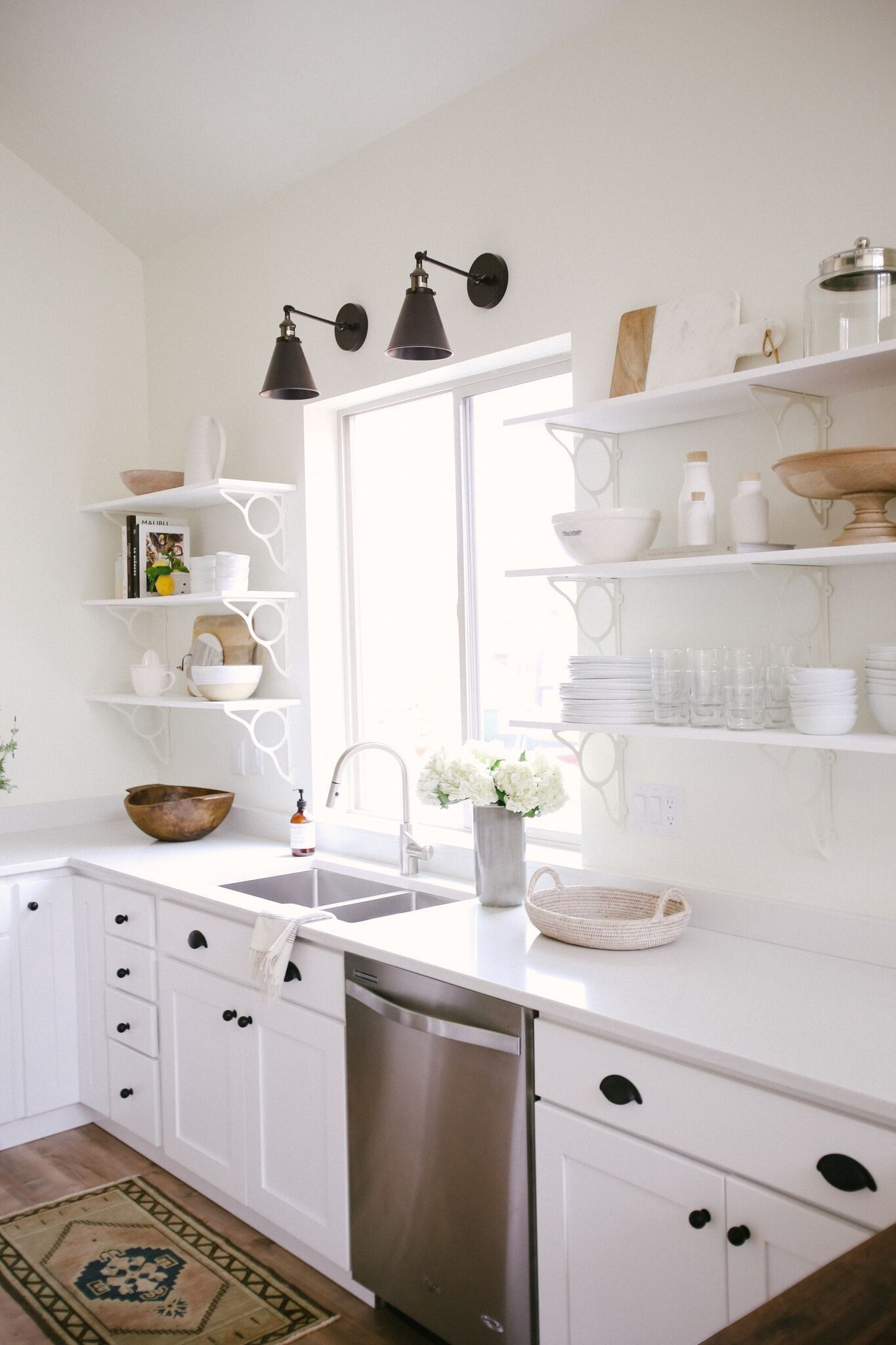A Clean Smart And Chic White Kitchen Nook With Small Wall Sconces