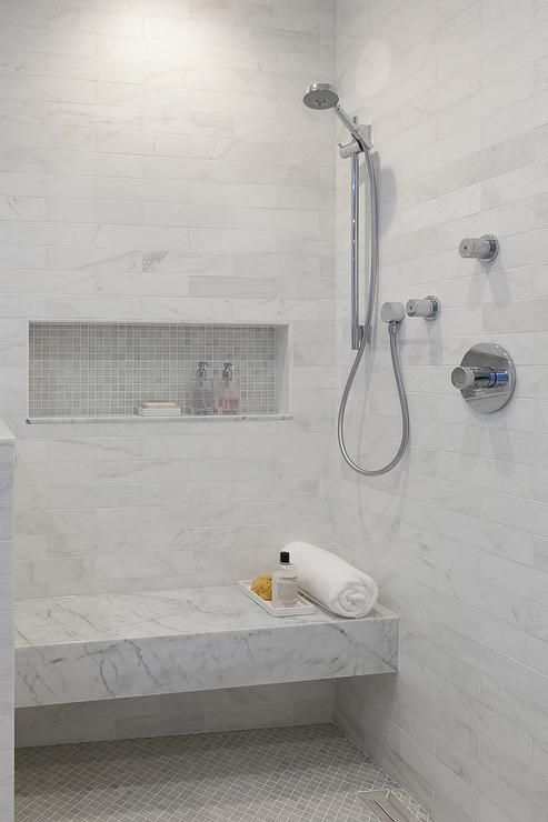 Gray marble grid tiled shower niche displayed over a thick