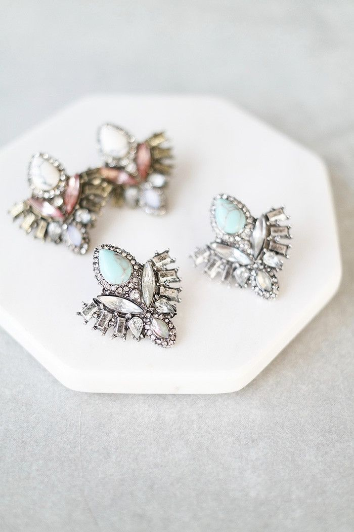 "Crystals and stones set in silver or gold on stud earrings. Details: - 1.25"" drop - 1"" wide - Post back"