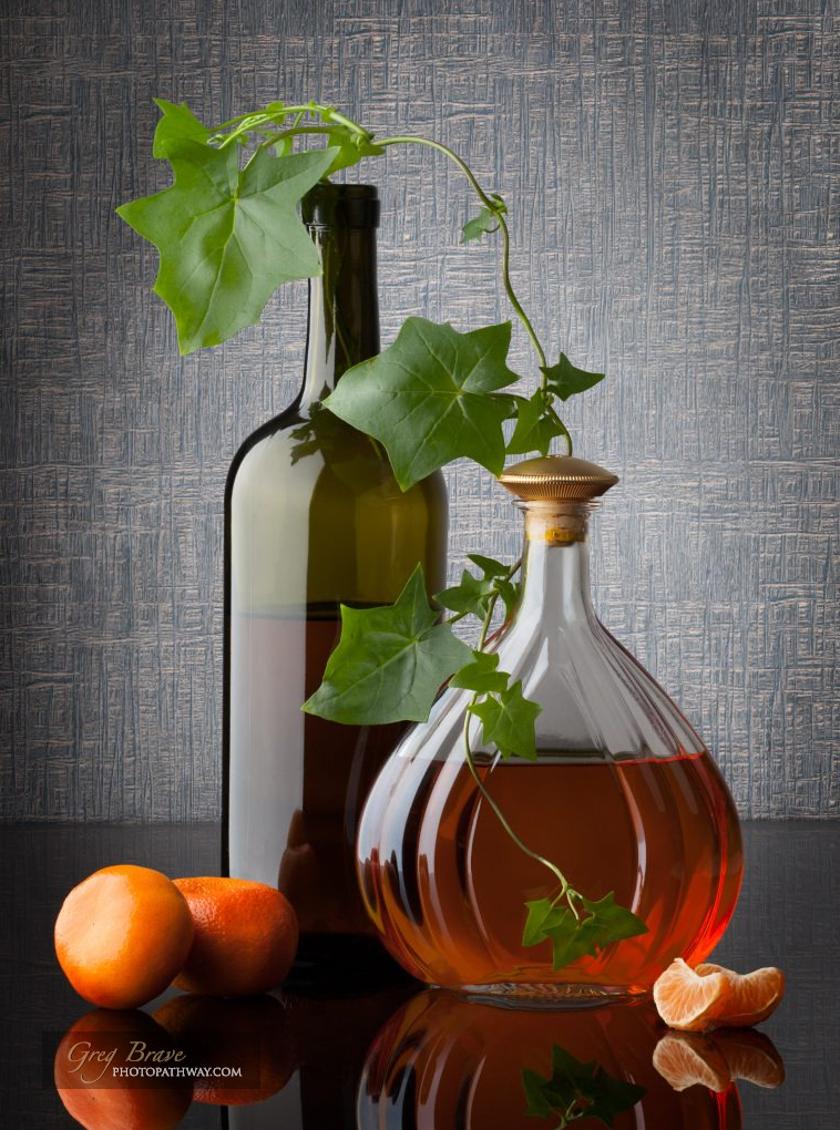 Still life composition with bottles leafs and mandarins on ...