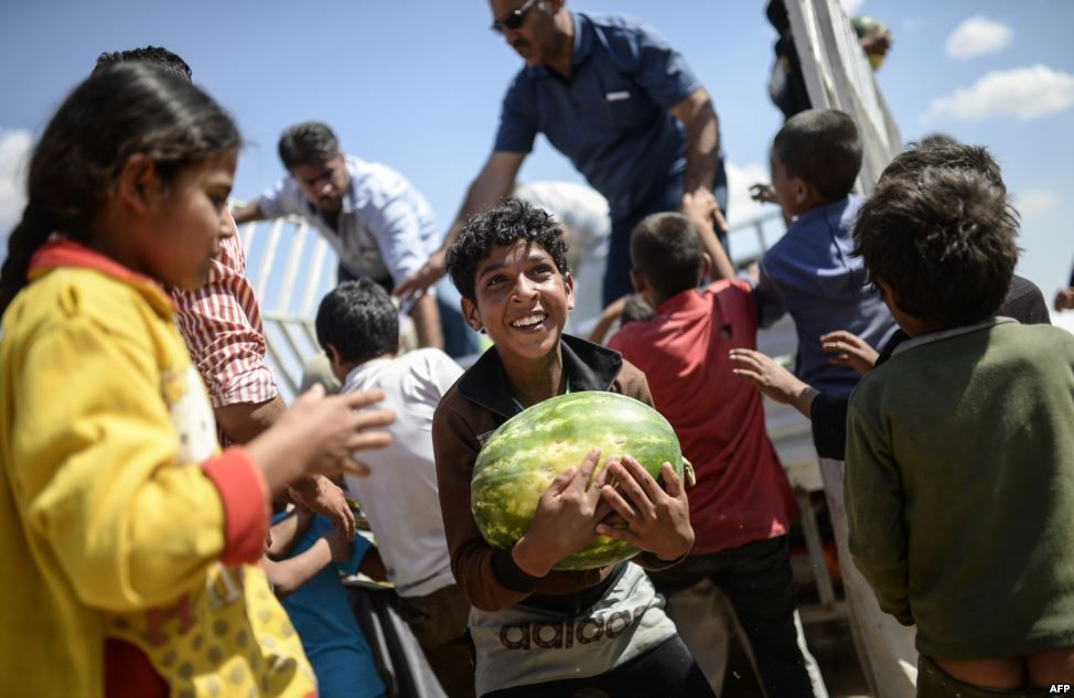 #refugee #crisis #Syria A Syrian boy holds a watermelon distibuted near the Akcakale crossing gate between Turkey and Syria at Akcakale in Sanliurfa province.