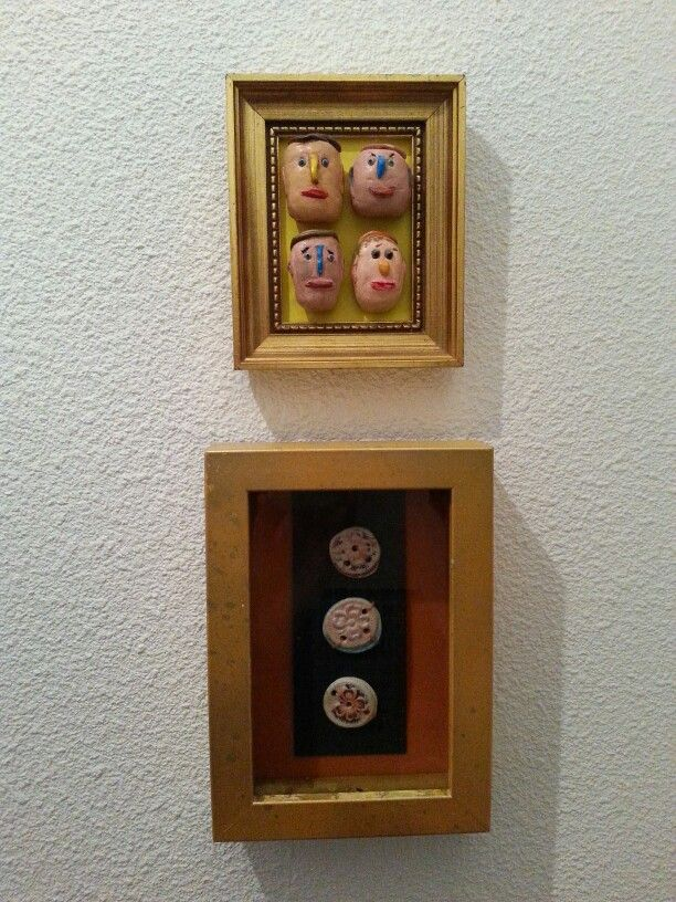 Little clay heads in frame by Madeleine Daniels