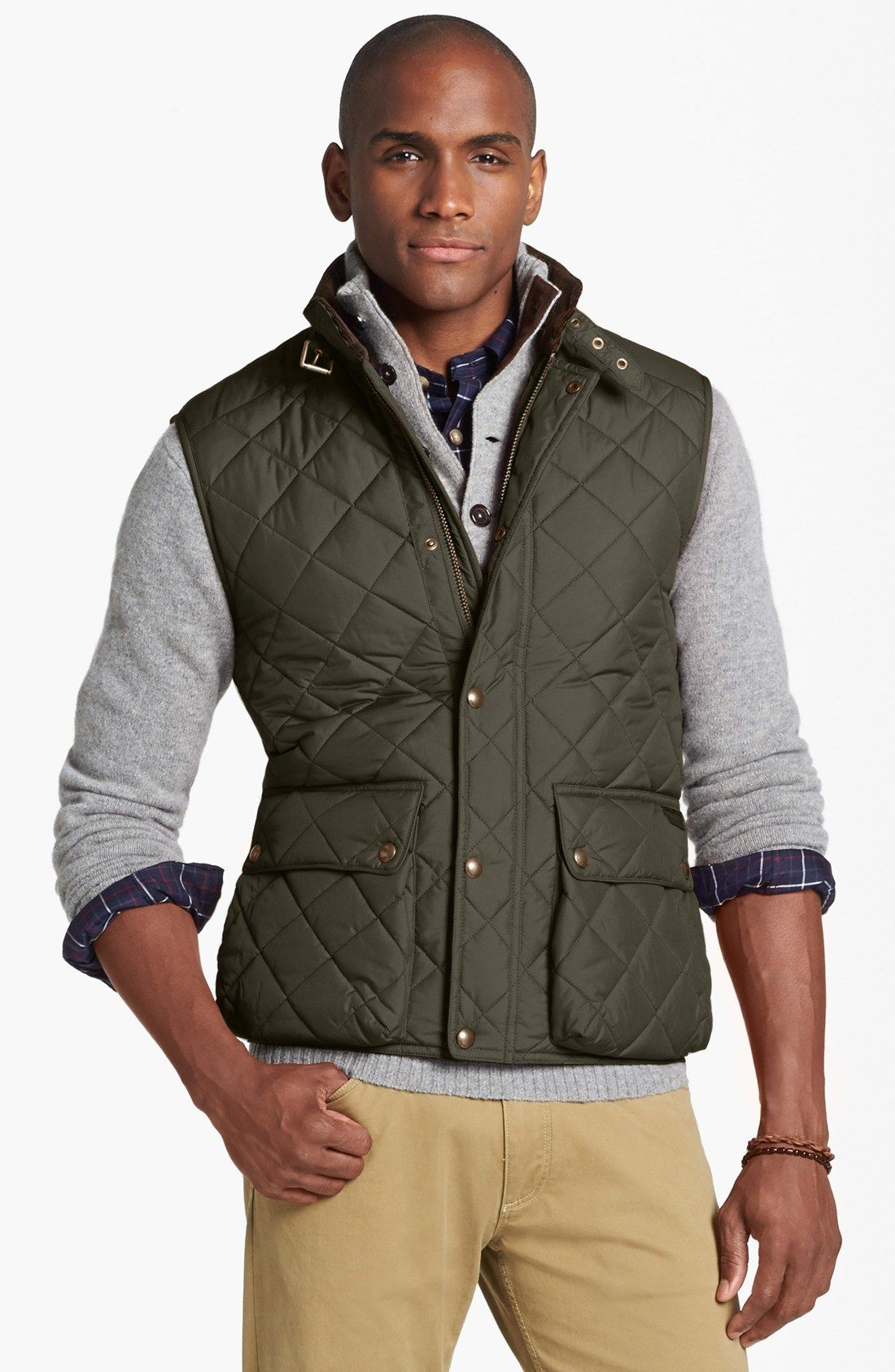 An olive green quilted gilet and tan chinos feel perfectly suited for weekend activities of all kinds.   Shop this look on Lookastic: https://lookastic.com/men/looks/gilet-henley-sweater-long-sleeve-shirt/15800   — Navy Plaid Long Sleeve Shirt  — Grey Henley Sweater  — Olive Quilted Gilet  — Brown Bracelet  — Khaki Chinos
