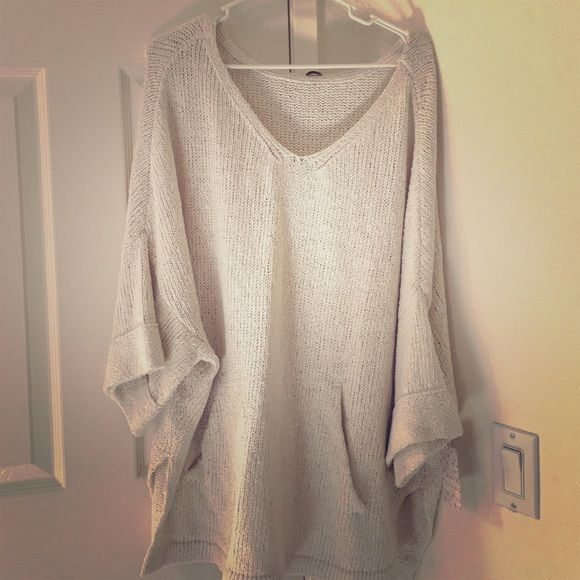 Loose pullover sweater Beige colored loose pullover sweater.  40% cotton 40% acrylic ... Size says Medium but runs really big so I would say it's more Large/ xlarge.  Brand new.  Never worn.  Super comfy.  Has pockets on the front. Free People Sweaters Shrugs & Ponchos