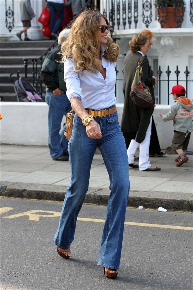 Elle Macpherson con jeans, blusa blanca y altos zapatos de tacón