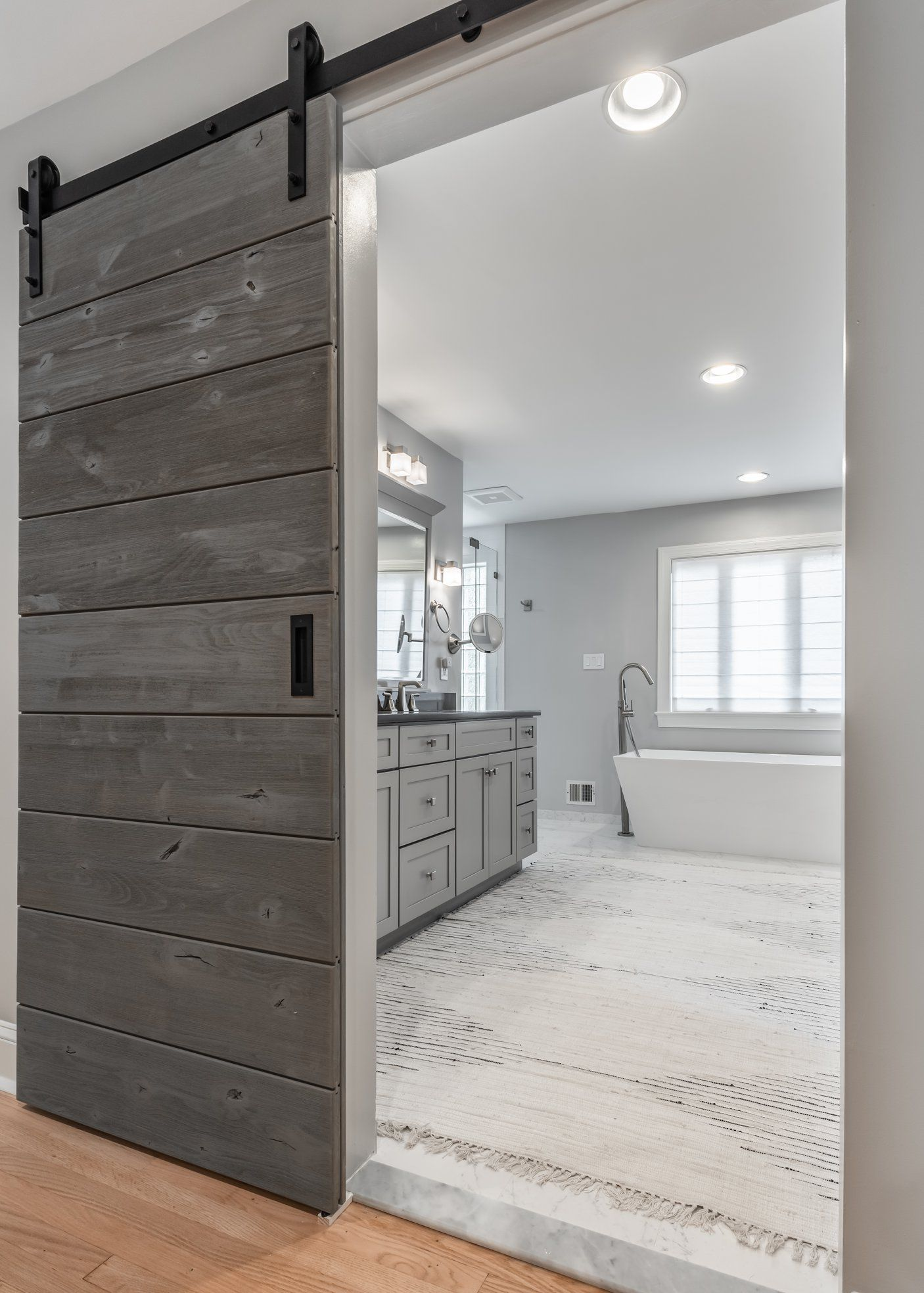 A Knotty Alder Horizontal Barn Door In A Driftwood Grey Finish Hanging On Black Classic Sliding H In 2020 Barn Door Designs Interior Barn Doors Sliding Doors Interior