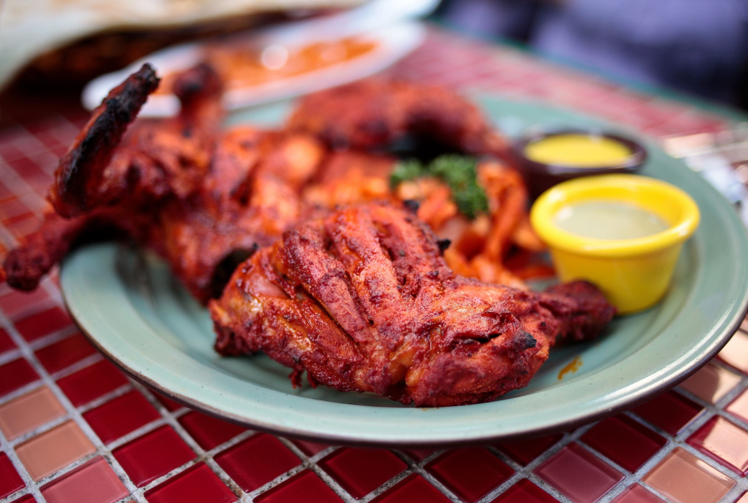 Tandoori chicken (India) Cooked in a clay oven called tandoor, it is roasted chicken marinated in yogurt and seasoned with turmeric and red chilli powder