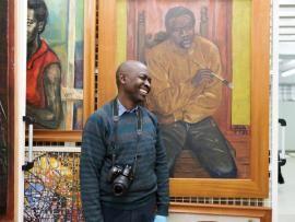 Prof. George Kyeyune in der Gegenwartskunst-Sammlung Afrika des Weltkulturen Museums. Foto: Wolfgang Günzel.