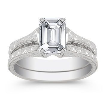 6.9mm x 4.8mm Emerald cut White Sapphire  A vintage inspired engraved design gives this modern wedding set style and elegance. Crafted from superior quality 14 karat white gold, this piece's delicate feminine lines create the perfect backdrop for the center diamond of your choice. Shown with a center stone Emerald Cut White Sapphire.