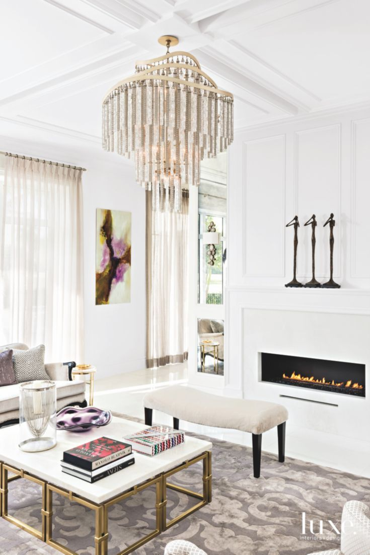 White Living Room with Glamorous Gold Fireplace and Chandelier ...