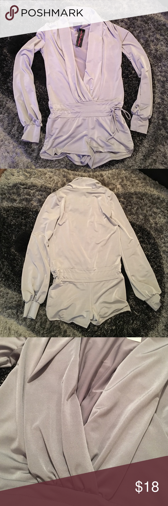 Metallic silver deep v Romper Brand new, NEVER WORN. Metallic silver romper with a deep v neck. Long sleeves, and tie around he waist to make tighter or looser. Shiny stretchy material. The romper is pretty short as you can see in the picture. Other