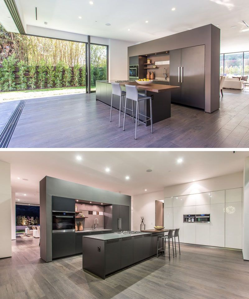 This kitchen opens up completely to the backyard, perfect for entertaining. A partial wall separates the kitchen from the dining and living area. It also has an island with a cantilevered wooden counter, making room for bar stools.