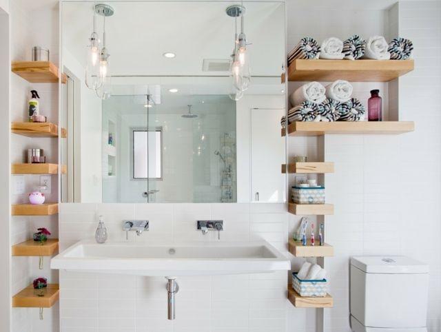 une petite salle de bains blanche avec des étagères en bois clair