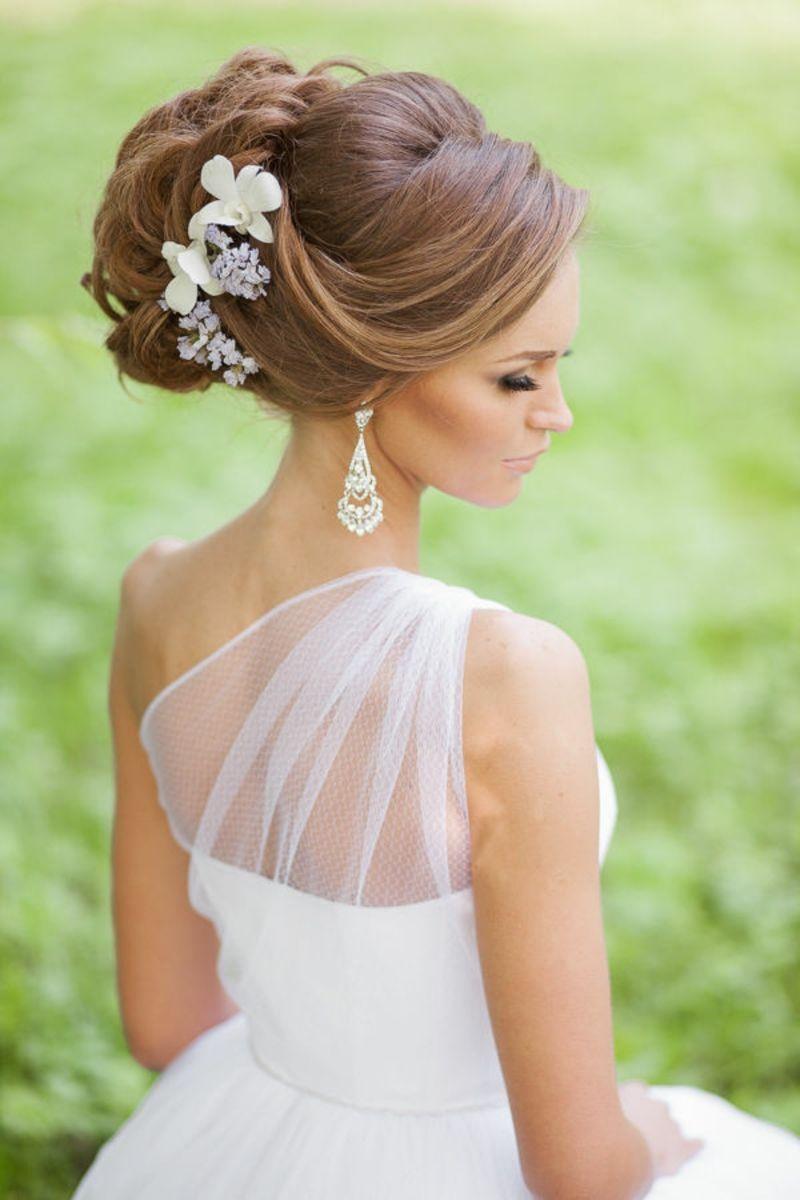 Brautfrisuren seitlich offen gesteckt  Brautfrisur Dutt mit dekorativen künstlichen Blumen seitlich ...
