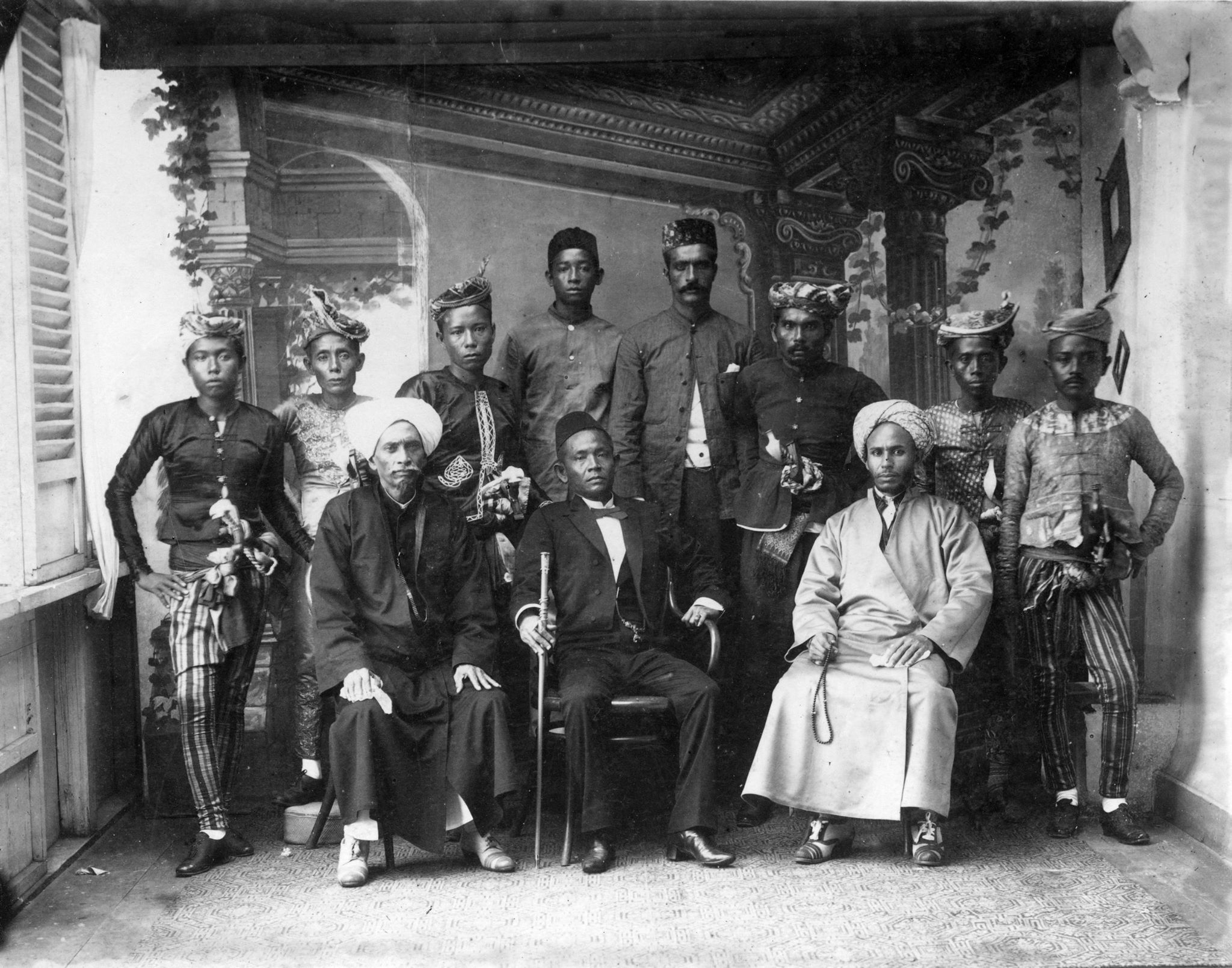 The Sultan of Sulu seated center with walking stick and fez. He is accompanied by high status moros and his religious advisor. Note that all the men are wearing shoes. This was a status symbol only the highest rank could enjoy. Most men and women in Jolo went barefoot.