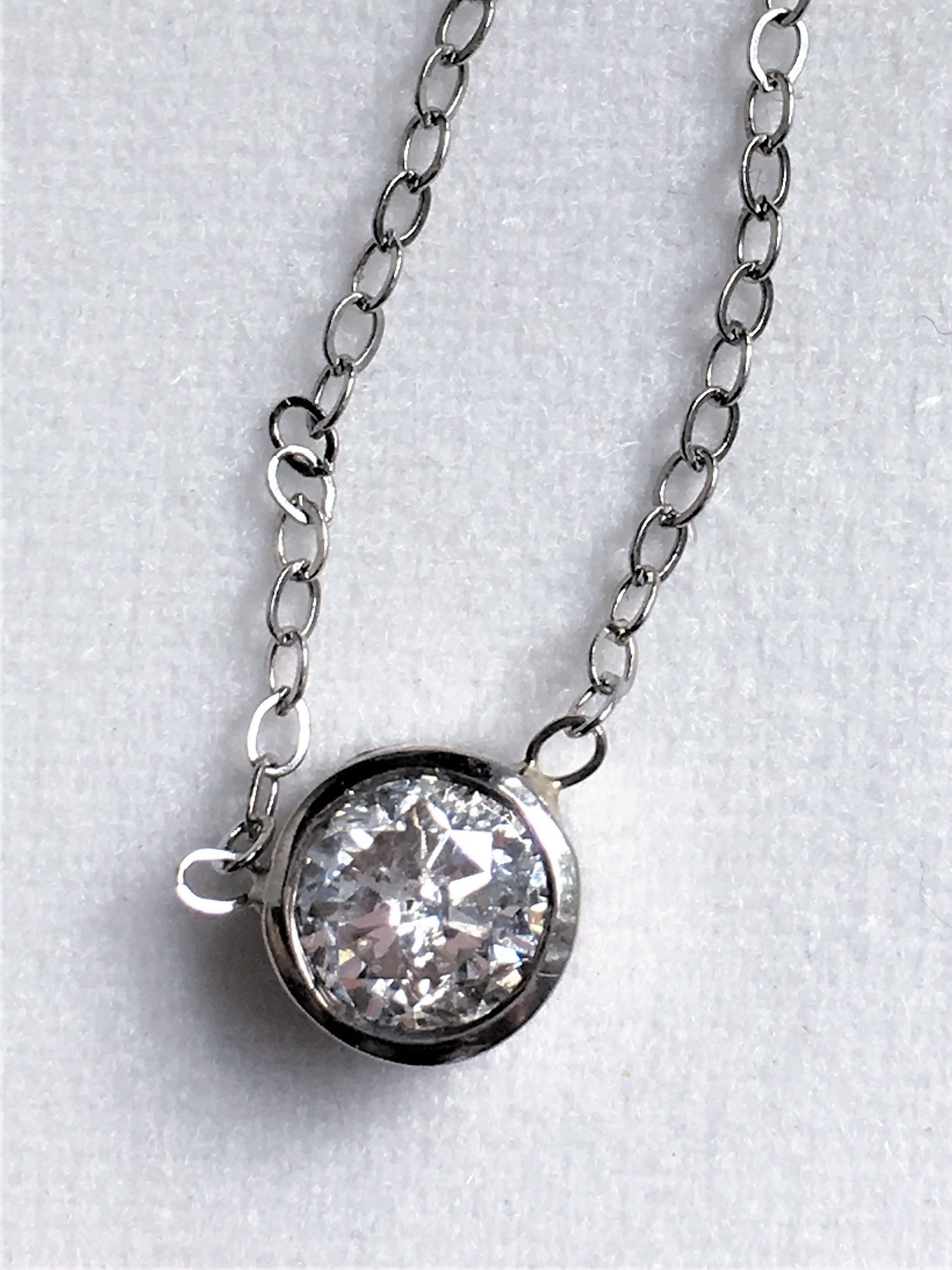 White gold bezel set diamond pendant on a