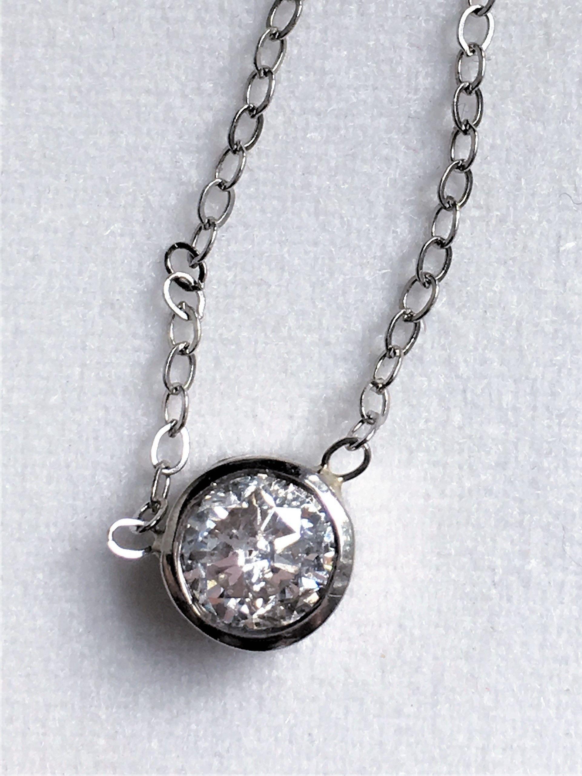 White gold bezel set diamond pendant on a