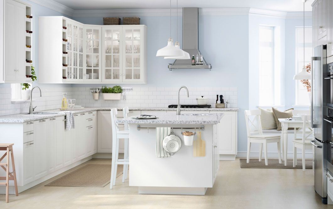 A large white kitchen with a lot of drawers, wall cabinets and a ...