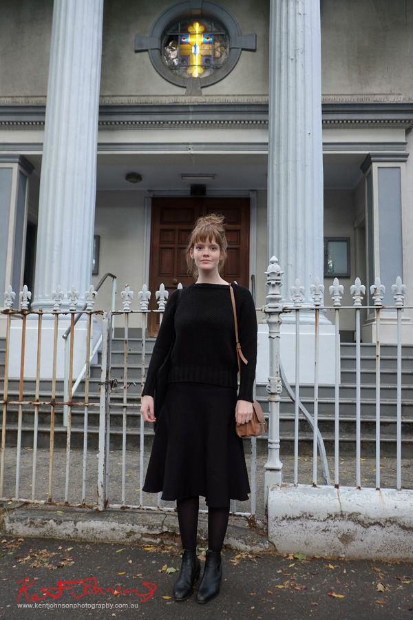 Young woman with auburn hair in black knit jumper black skirt and stockings with RM Williams cuban heel boots, tan stachel/shoulder bag, photographed outside the Greek Orthodox Church on South Dowling Street for Street Fashion Sydney.