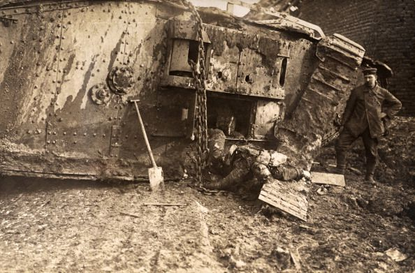 A German soldier standing beside the remains of a British Tank that had been knocked out by artillery fire during German counter attacks near Cambrai, ca 1917.